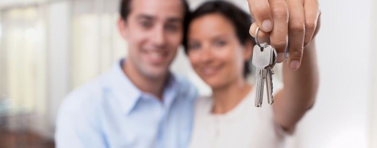 Image of a racially ambiguous, heterosexual, couple holding keys to their new apartment.